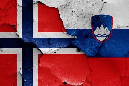 flags of Norway and Slovenia painted on cracked wall