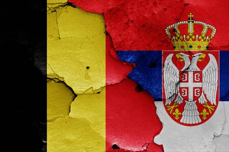 flags of Belgium and Serbia painted on cracked wall