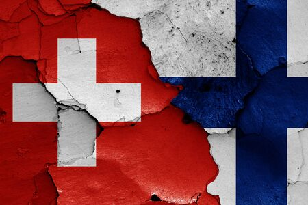 flags of Switzerland and Finland painted on cracked wall Zdjęcie Seryjne