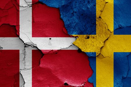 flags of Denmark and Sweden painted on cracked wall