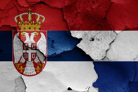 flags of Serbia and Nettherlands painted on cracked wall