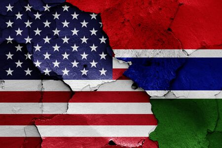 flags of USA and Gambia painted on cracked wall Zdjęcie Seryjne