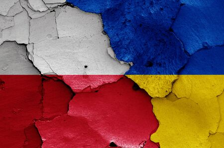 flags of Poland and Ukraine painted on cracked wall