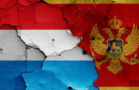 flags of Luxembourg and Montenegro painted on cracked wall 免版税图像