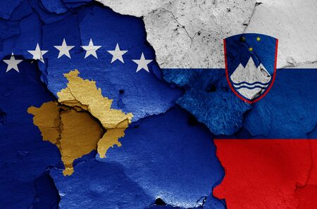 flags of Kosovo and Slovenia painted on cracked wall 免版税图像