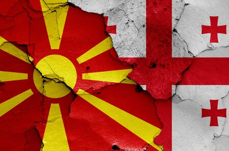 flags of North Macedonia and Georgia painted on cracked wall 免版税图像