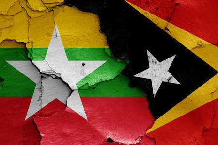 flags of Myanmar and East Timor painted on cracked wall