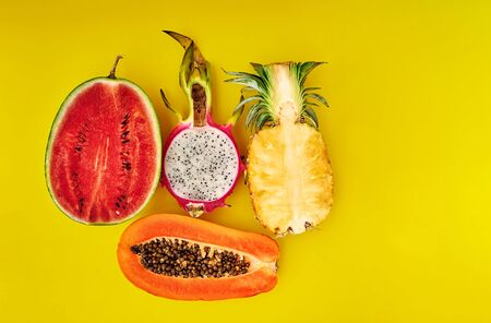 Half tropical fruits of pineapple, papaya, watermelon, dragon on a yellow background. Minimal style. Space for text