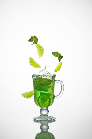 Lime slices and mint leaves splash into an ice cocktail