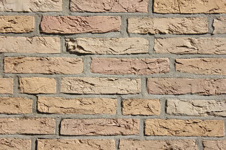 Brick wall light brown big stones gray mortar