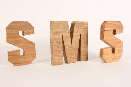 naturholz: SMS text from wood letters Holz Buchstaben white Background