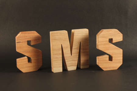 SMS text from wood letters Holz Buchstaben black Background Stock Photo - 16995973
