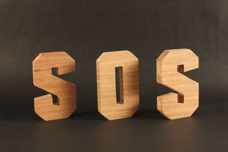 SOS text from wood letters Holz Buchstaben black Background