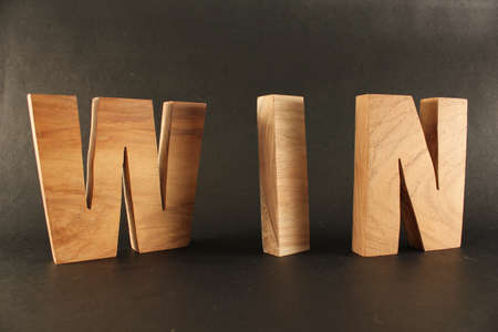 naturholz: WIN text from wood letters Buchstaben black Background Stock Photo