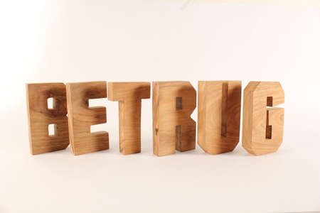 buchstaben: Betrug text from wood letters Holz Buchstaben white Background Stock Photo