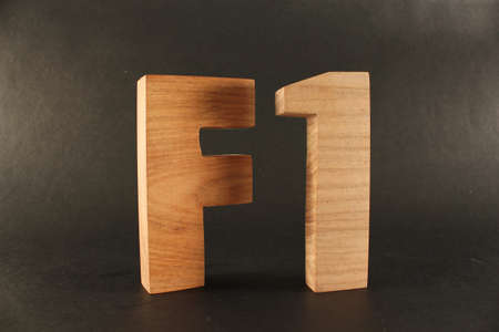 buchstaben: F1 text from wood letters Holz Buchstaben black Background