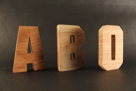 naturholz: ABO text from wood letters Holz Buchstaben black Background