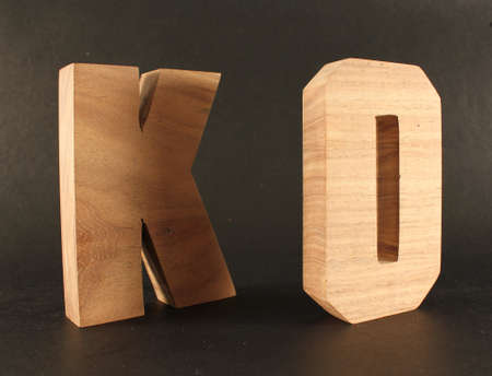 naturholz: KO text from wood letters Buchstaben black Background
