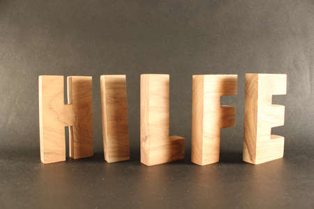 buchstaben: Hilfe text from wood letters Holz Buchstaben black Background
