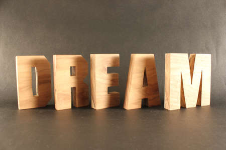 naturholz: Dream text from wood letters Holz Buchstaben black Background Stock Photo