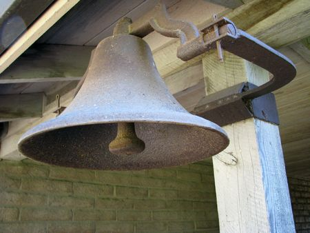 fixed: An old metal farm bell fixed to a post.
