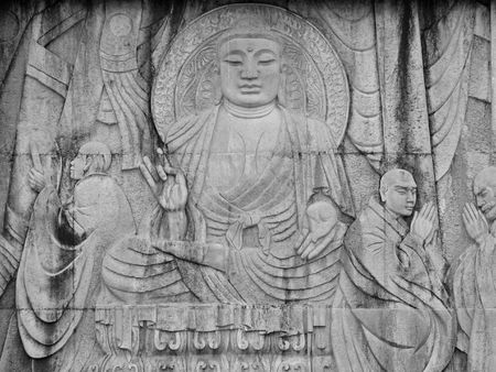 A carved relief of Buddha teaching the Dharma specifically relating to the first transmission of Buddhism in to China. Stock Photo