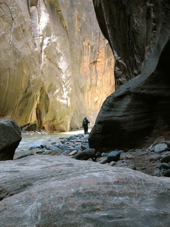 A hiker going around the corner in the Narrows of Zion Canyon.  Utah, U.S.A.