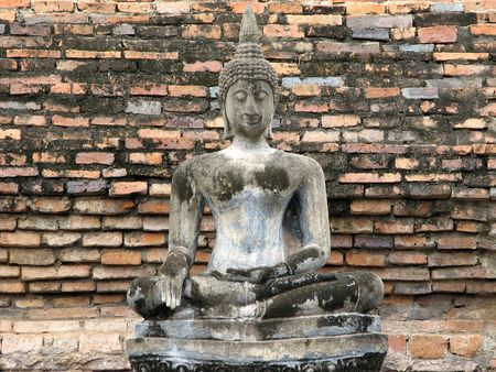 seated: A seated concrete Buddha statue in front of an ancient brick wall in sukhothai National Park.  Sukhothai, Thailand.