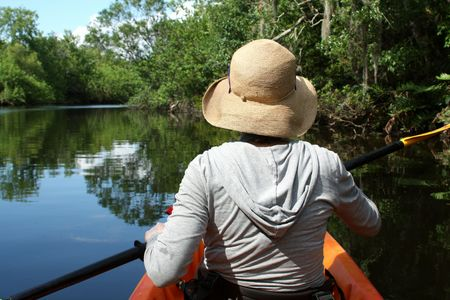 A young woman exploring a florida swamp in a kayak on a sunny day.  Melbourne, Florida. 免版税图像