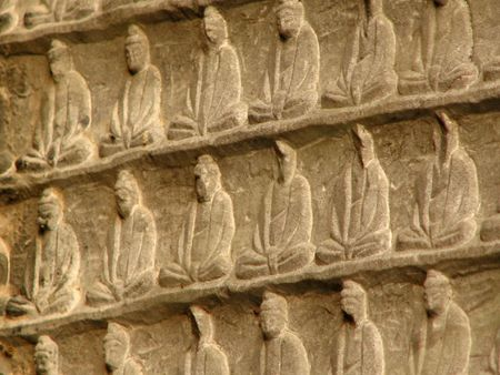 wei: A stone carved background representing an infinite number of Buddha figure.  Part of The Wall of A Thousand Buddhas in Longmen caves outside Luyang, China.