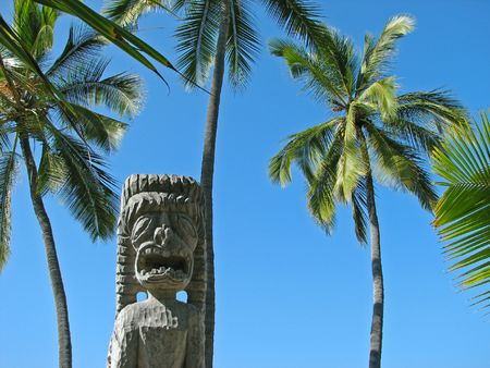 A wooden Tiki statue with large coconut palm trees on the Big Island, Hawaii.
