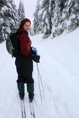 A young lady dressed in red skiing in the mountains of Oregon, USA.
