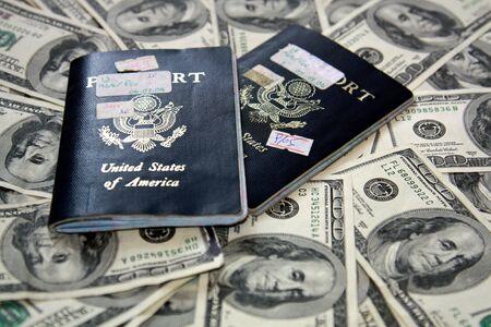 100 ドル札の散乱の上に 2 つのアメリカ合衆国のパスポート。