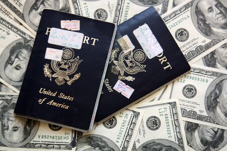 Two United States of America passports on top of a scattering of hundred dollar bills. Фото со стока
