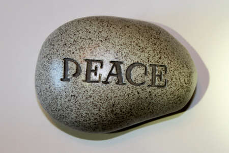 One Word Says It All.  A small rock used as a paper weight. The word peace is engraved.
