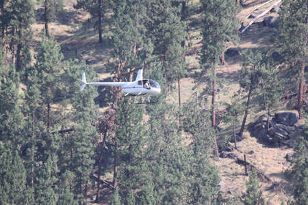 Helicopter Flying Through Valley. This helicopter Pilot is coming in for a landing at the local airport.