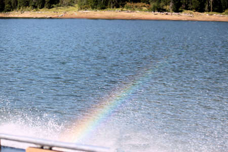 Rainbow in the mist. This is a Rainbow created by the wake of a moving boat on Dworshak lake in Idaho. Stock Photo
