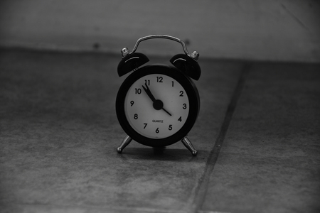 A stopped black and white alarm clock on a tiled floor