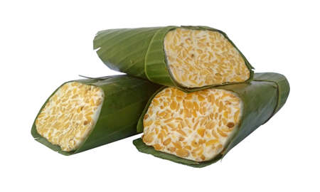 Tempe soybeans fermented wrapped with banana leaf on white Stock Photo