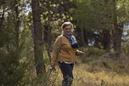 Senior woman walks looking for thyme and fragrant plants through the Santuario de Misericordia, near Borja, in the province of Zaragoza, Spain. Stock fotó