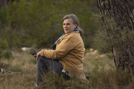 Senior woman rests sitting after a walk in the Sanctuary of Mercy, near Borja, in the province of Zaragoza, Spain. Stock Photo