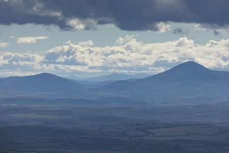 Landscape of mountains with clouds in the Moncayo area and the Iberian mountain system, looking towards Cabezo de Los Frailes in the Tabuenca area, Talamantes, near Borja, Zaragoza province. Stock Photo