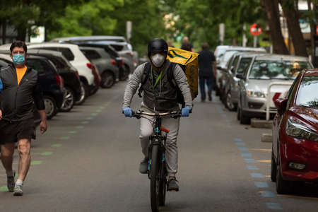 Madrid, Spain - May 19, 2020: Delivery people from the home delivery company, Glovo, working on the streets of Madrid, delivering food at rush hour. Редакционное