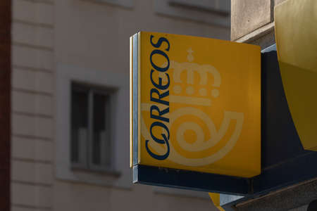 Madrid, Spain - May 19, 2020: The entrance sign to a post office on Calle Ibiza, in the Retiro district. They offer parcel, collection, shipping and other national and international services.