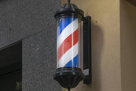 Classic barber pole with red, white and blue stripes, located on the facade of a building, on Calle Doce de Octubre, a commercial area of Madrid.