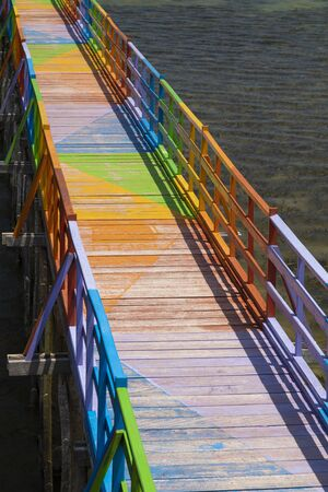Wooden promenade decorated with vibrant and diverse colors, facing the sea and among the mangroves, in the city of Wakai, in the Togean Islands, Indonesia.