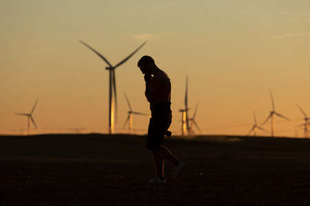 A man walks talking on the phone in the countryside at sunset, after taking pictures of distant wind turbines, on the horizon.