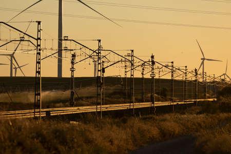 Train tracks superimposed on a landscape of silhouettes of operating wind turbines m in the Ribera Alta del ebro, in Aragon, Spain.