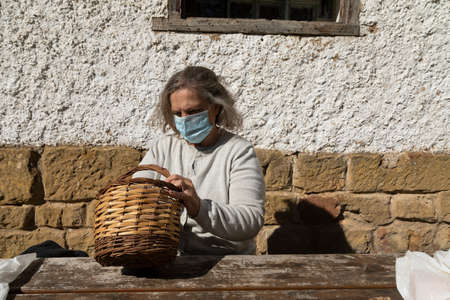 A senior adult woman, wearing a face mask, searches for something in a wicker basket before eating in front of the mountain hut of the fountain of Artica, in Luesia, Spain.