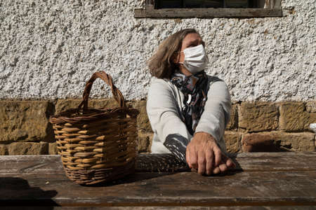 A senior woman, wearing a white protective face mask, stretches her arms and relaxes, near the mountain hut of the fountain of Artica, in Luesia, Spain.